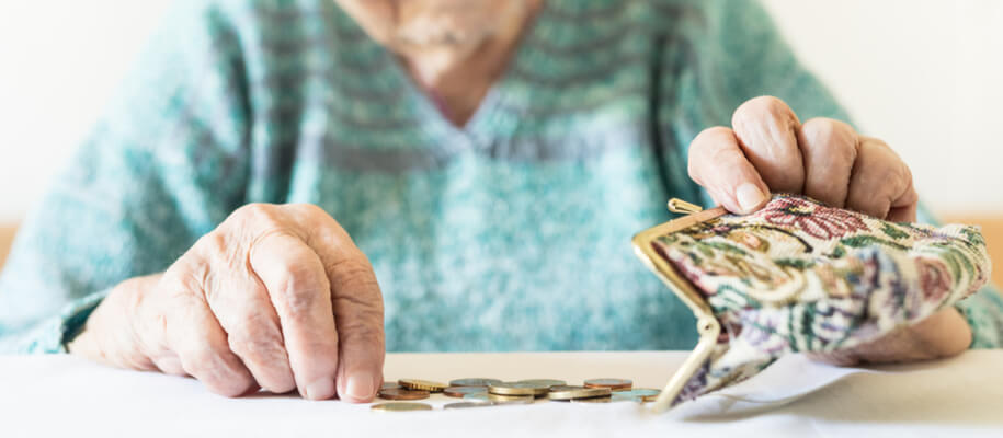 Elderly woman opens her coin purse over a table while counting the coins.