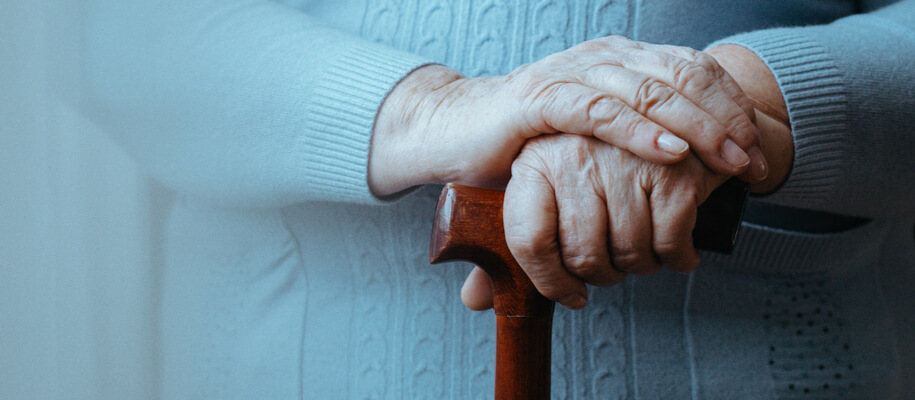 An elderly woman's hands are placed on top of her cane as she contemplate respite care options.
