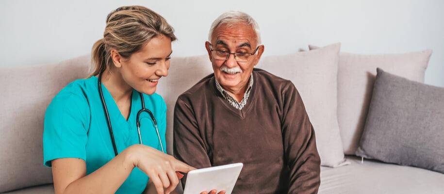 A nurse shows a senior man something on a tablet.
