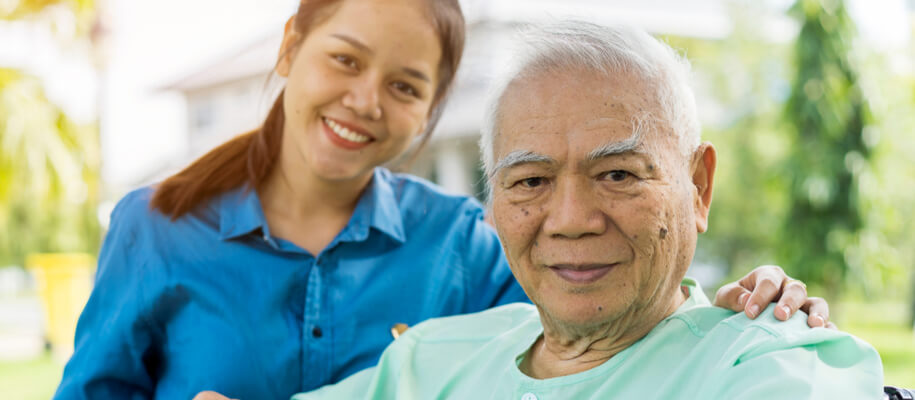 A woman caregiver smiling standing next to a senior resident.