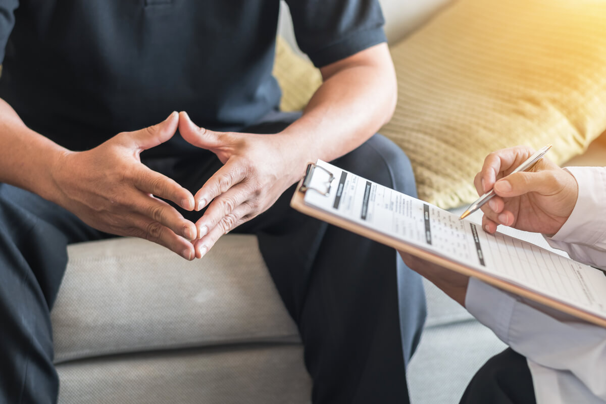 A patient and staff engaging in mental health care in a transitional facility.
